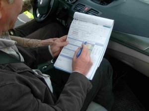 l'inspecteur note sur un papier les observations lors de la conduire