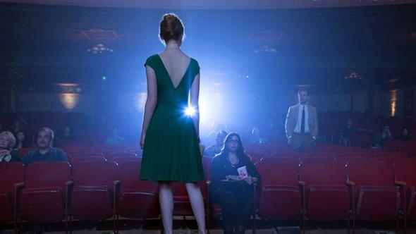 Emma stone éclairée par une lumière de salle de cinéma