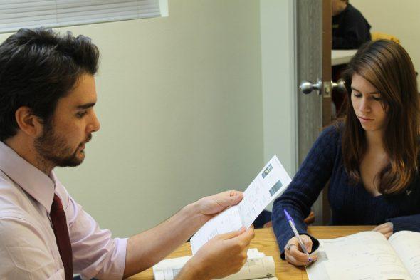 Un étudiant aide un autre étudiant à réviser au tutorat